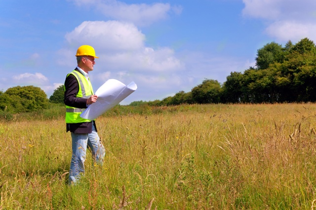 Architect wearing site safety gear and holding plans surveying a new building plot
